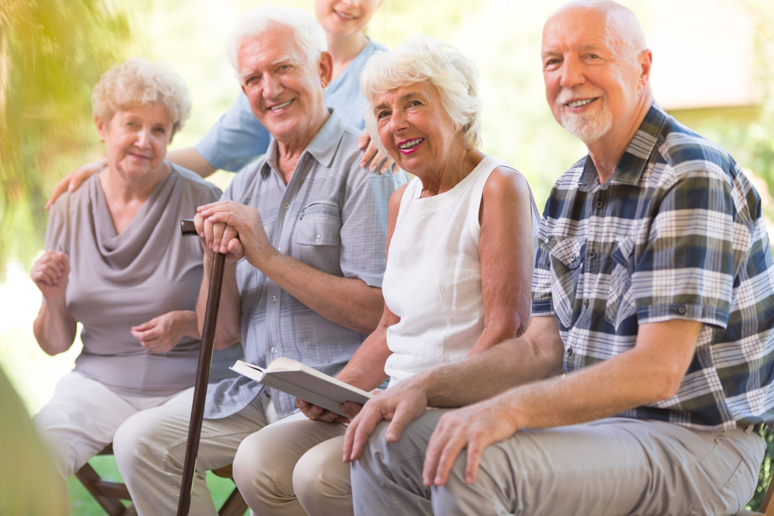 Group of elders smiling and sitting outside with a book