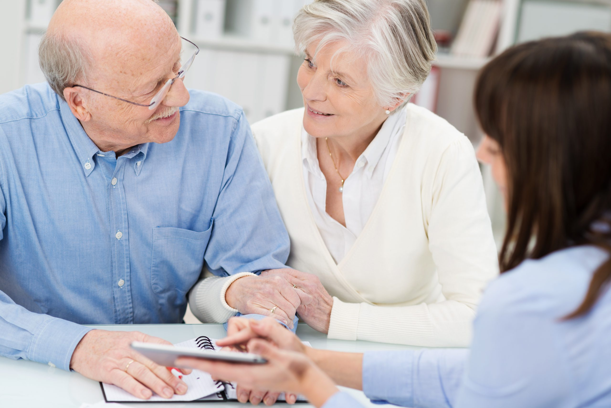 Affectionate elderly couple in a business meeting holding hands as they discuss a proposal put forward by their broker